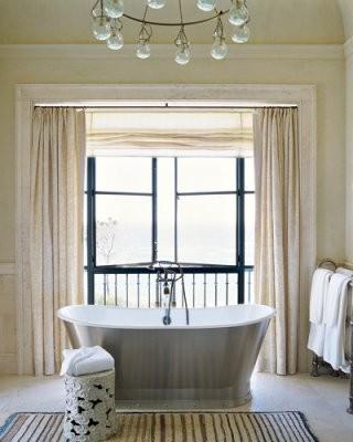 un bagno beige e cremoso con una grande finestra che brilla molta luce naturale all'interno