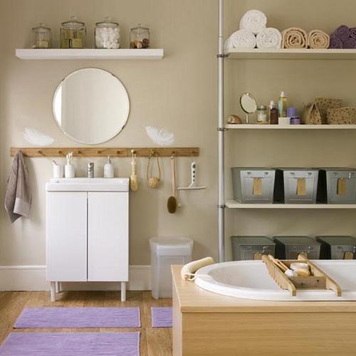un bagno in legno color talpa e chiaro con alcuni mobili bianchi e acciaio inossidabile