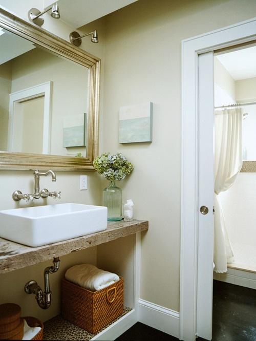 un bagno beige e bianco con una superficie di vanità rustica e uno specchio con cornice dorata