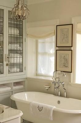 un bagno cremoso e bianco sporco con opere d'arte in cornici scure per uno spazio chic