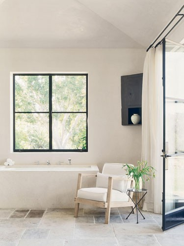 un bagno cremoso e beige con tocchi scuri e adorabile fascino vintage oltre a una disposizione verde