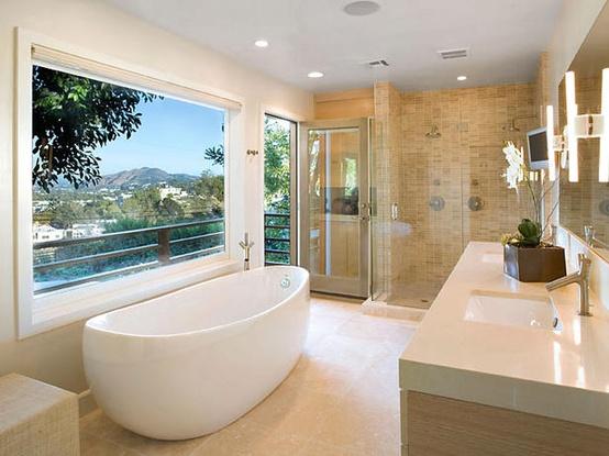 un bagno beige, tortora e bianco con una grande finestra per la vista, fiori in vaso e vari tipi di piastrelle