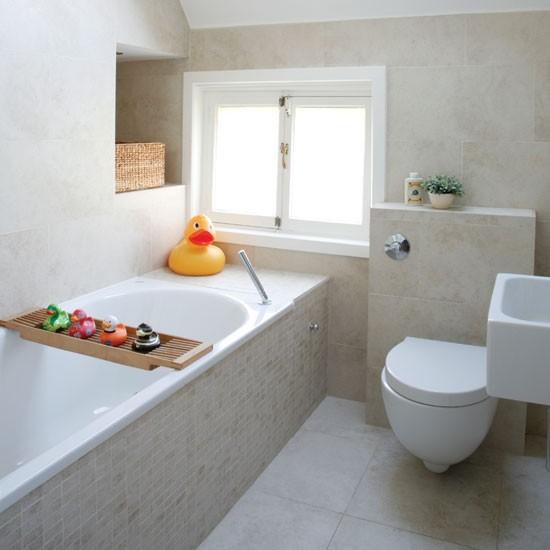 un bagno beige chiaro rivestito di piastrelle, con elettrodomestici bianchi e accessori colorati e stravaganti