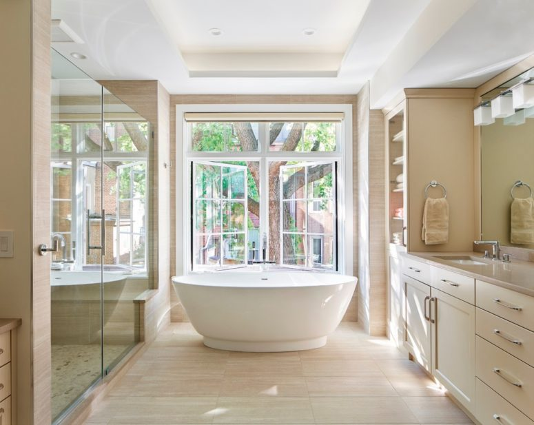 un bagno tortora e beige con una grande finestra per godersi il panorama e riempire lo spazio di luce naturale (Terra Studio)