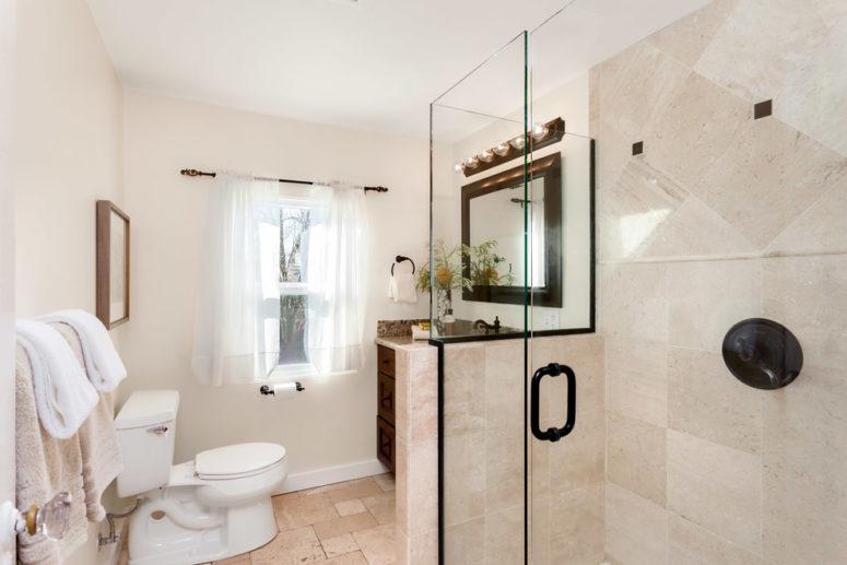 un bagno beige e cremoso con elettrodomestici bianchi e tocchi di nero per il dramma (Seattle Staged to Sell and Design LLC)
