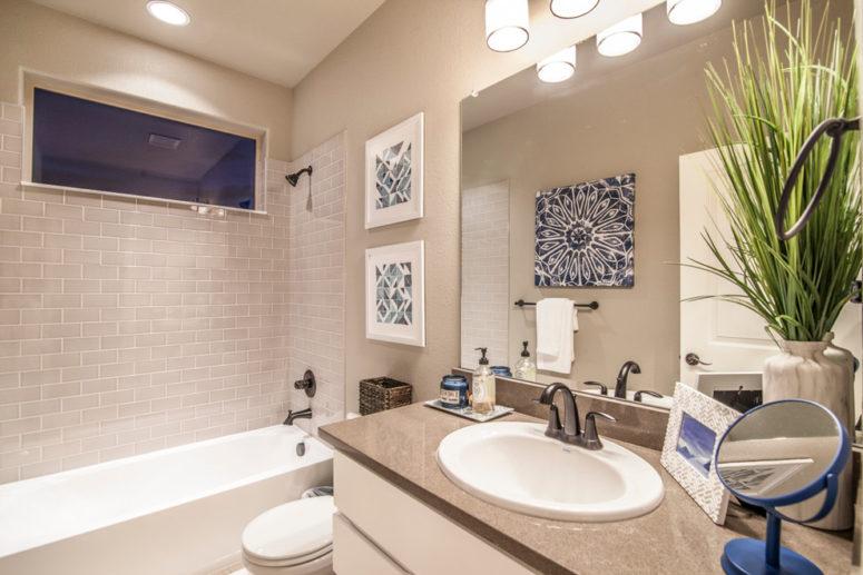 un bagno color talpa con elettrodomestici e superfici bianche che rinfrescano lo spazio e la vegetazione in vaso aiuta anche in questo (Amy Laner Anjo Designs)