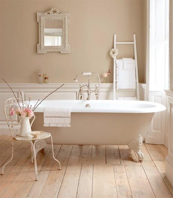 un bagno color talpa e beige molto rilassante e tranquillo con mobili vintage e una vasca da bagno con i piedini