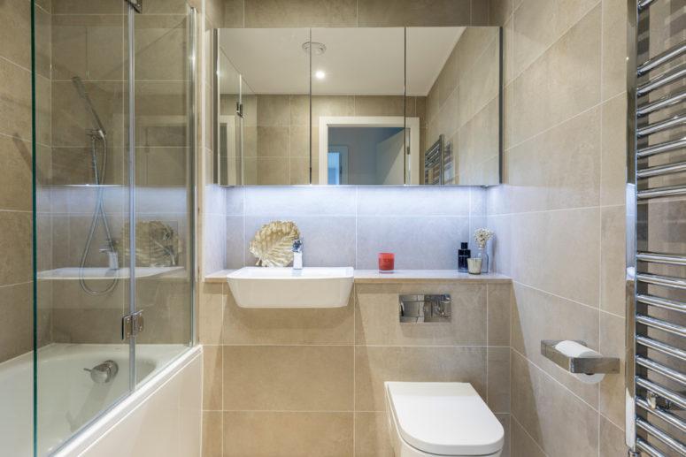 una camera da letto piccola e funzionale realizzata con piastrelle beige, tocchi di bianco e acciaio inossidabile (Anouska Tamony Designs- Architecture & amp; Interiors)