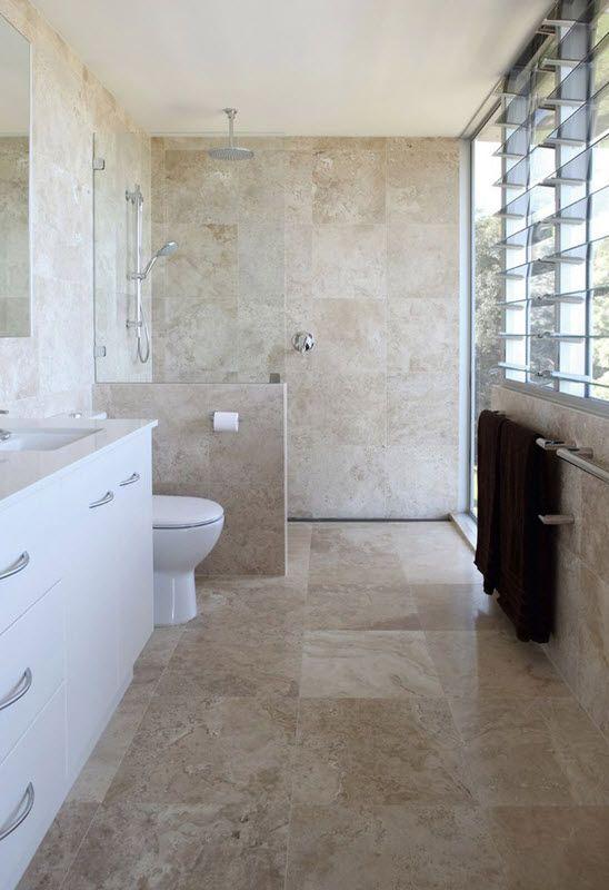 piastrelle beige ispirate alla pietra che ricoprono l'intero bagno, elementi bianchi e una vanità per un look elegante