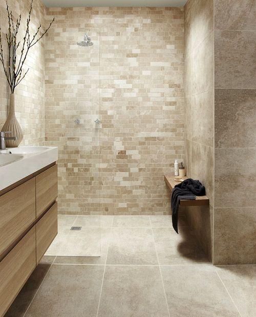 un bagno marrone chiaro e tortora rivestito con piastrelle di varie dimensioni, un lavabo beige e lavandini bianchi
