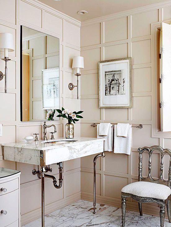 un elegante bagno beige fatto con pannelli a parete, mobili e lampade eleganti e un lavandino in marmo su gambe alte