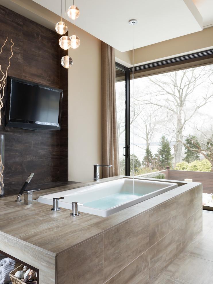 un bagno moderno fatto in taupe con una grande vasca rivestita di piastrelle beige e una finestra panoramica per la vista (Alexander Modern Homes)