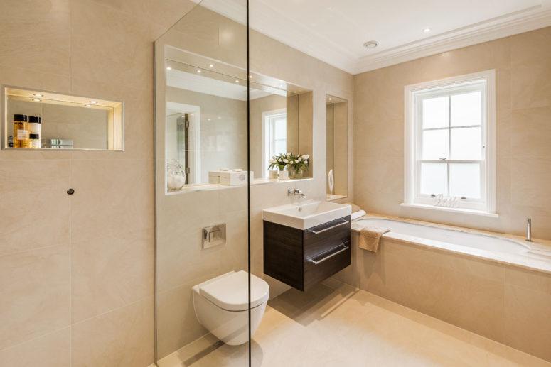 un bagno beige e tortora con elettrodomestici bianchi e una vanità scura per un contrasto e molta luce (Searchfield Homes)