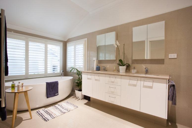 un bagno color talpa e crema con tappeti a strati, vegetazione in vaso e una finestra con ombre per mantenere la privacy (soluzioni di design urbano)