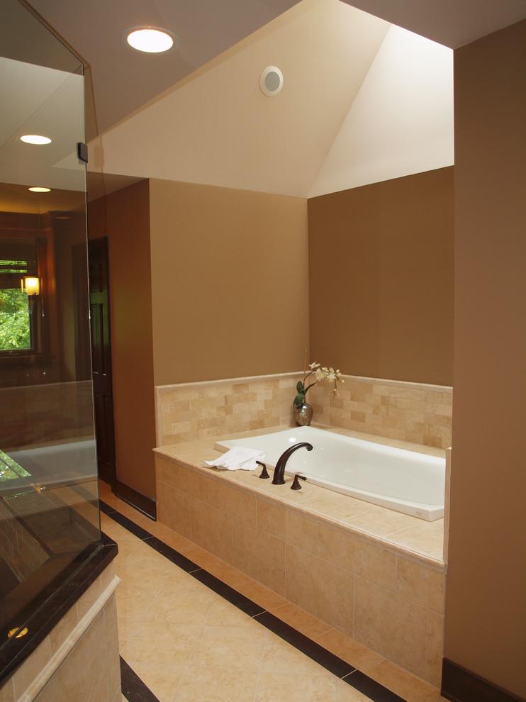 un tranquillo e accogliente bagno color talpa e beige con rubinetti scuri, piastrelle e una vasca da bagno bianca (rimodellamento della Normandia)