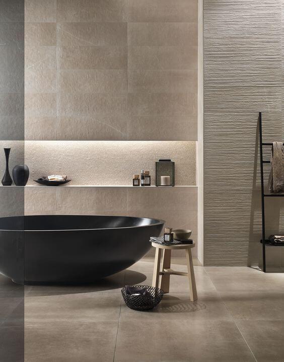 un lussuoso bagno beige con piastrelle e pannelli a parete materici, una vasca da bagno dakr e molte ciotole e tazze