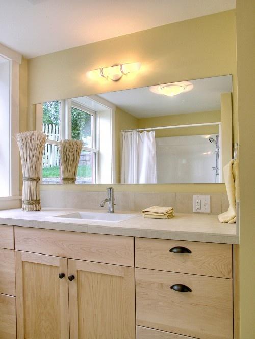 un bagno in legno giallo, beige e chiaro e tocchi di nero