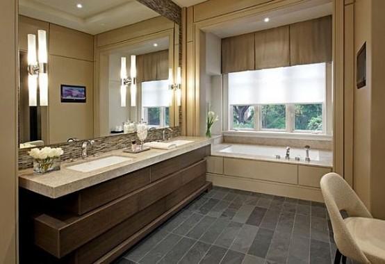 un bagno tortora, marrone, grigio e crema con una vanità scultorea, tende a strati e un grande specchio