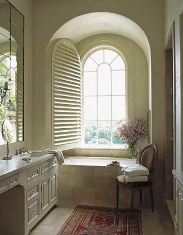 un bagno d'ispirazione vintage color crema e beige con una finestra ad arco e una vanità chic