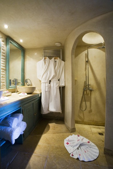 un bagno grigio talpa e verde acqua con uno spazio doccia ad arco e una vanità audace con ripostiglio