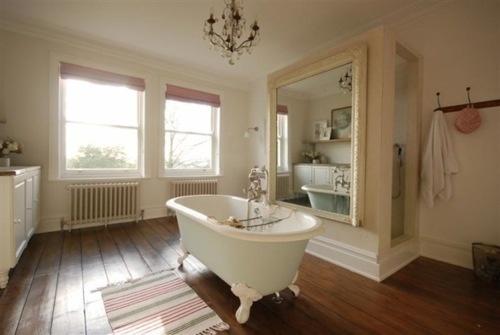 un bagno beige e crema, un pavimento in legno dai colori intensi e un grande specchio più finestre