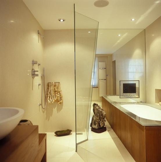 un bagno moderno beige chiaro accentuato con oggetti e luci in legno dai colori intensi e bianchi