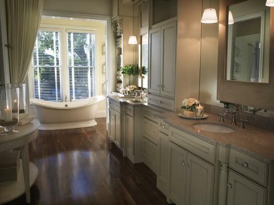 un bagno beige, crema e marrone con tende, un pavimento in legno scuro e una grande finestra