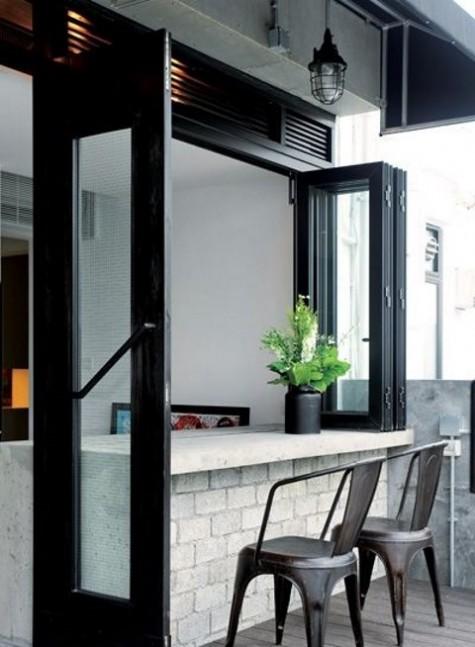 una finestra pieghevole con cornice nera e una zona colazione all'aperto o un bar passante con sedie in metallo
