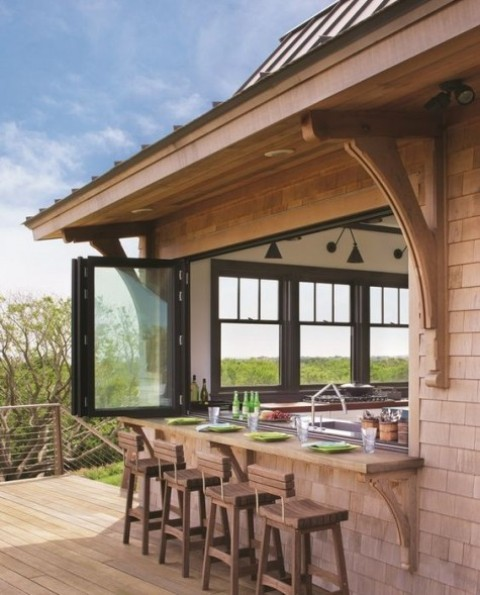una finestra pieghevole con cornice nera e un davanzale esterno macchiato di luce più sedie in legno