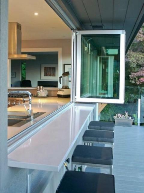 una semplice finestra pieghevole e uno spazio per la colazione all'aperto o una zona bar più comodi sgabelli con cuscini