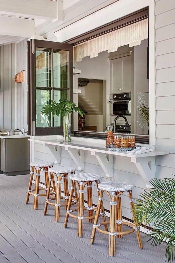 una finestra pieghevole con telaio marrone, un ripiano del tavolo bianco, sedie in rattan con sedili imbottiti e vegetazione in vaso