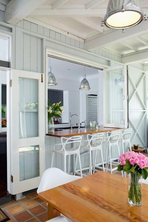 una finestra pieghevole con un ripiano del tavolo macchiato e sgabelli bianchi freddi per un bar all'aperto o uno spazio per la colazione