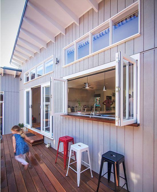 finestre pieghevoli con struttura bianca, un piano del tavolo macchiato di scuro e sgabelli in metallo colorato per una comoda zona all'aperto