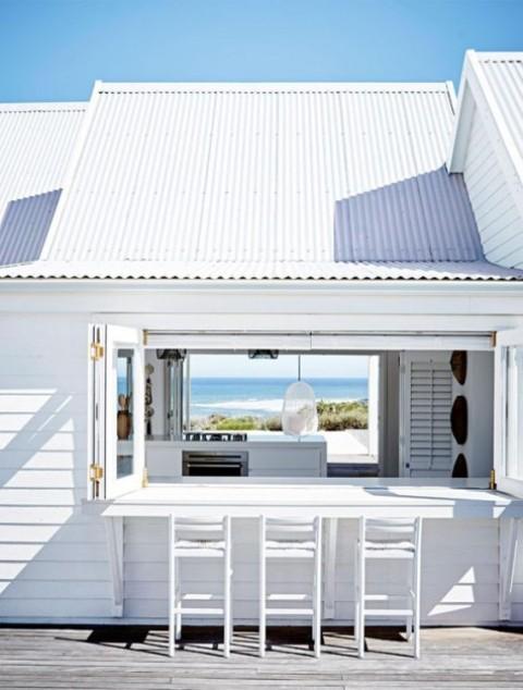 una semplice finestra pieghevole con cornice bianca e un ripiano del tavolo in legno bianco e sgabelli per una casa sulla spiaggia