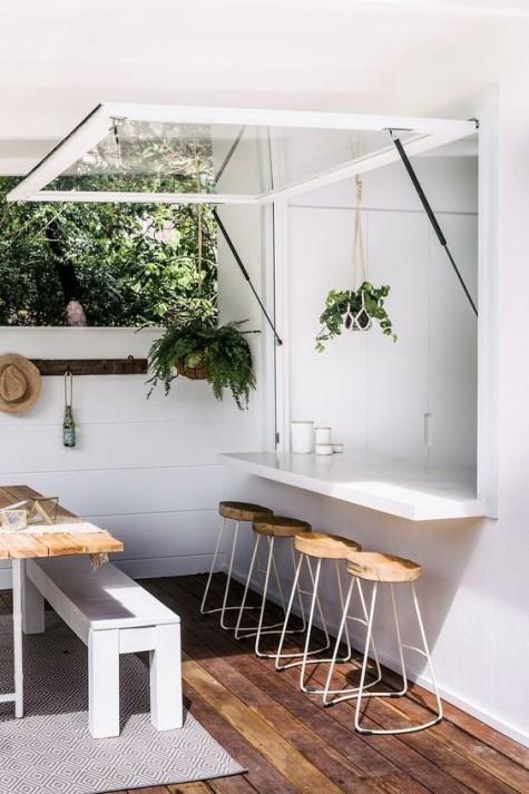 una finestra in stile garage con un piano del tavolo elegante e minimalista e alcuni sgabelli in legno e metallo