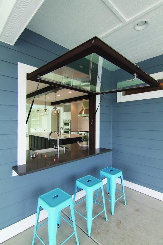 una finestra con cornice scura in stile garage, un ripiano del tavolo nero e sgabelli in metallo blu brillante per i pasti