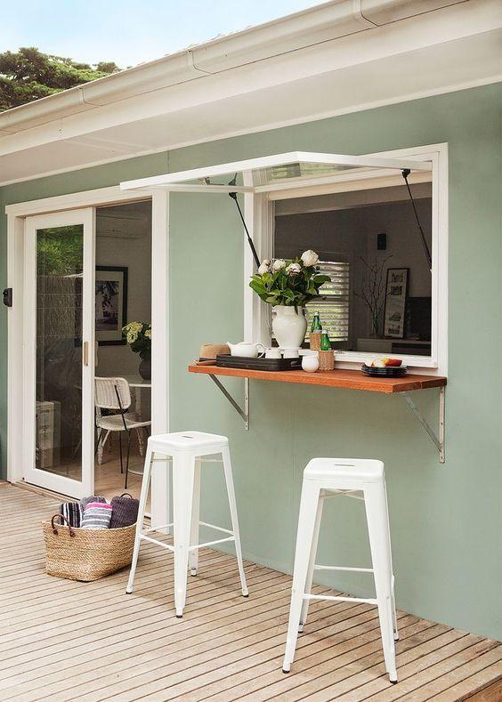 una finestra in stile garage, un piccolo ripiano del tavolo, sgabelli in metallo bianco per un bar all'aperto confortevole e accogliente