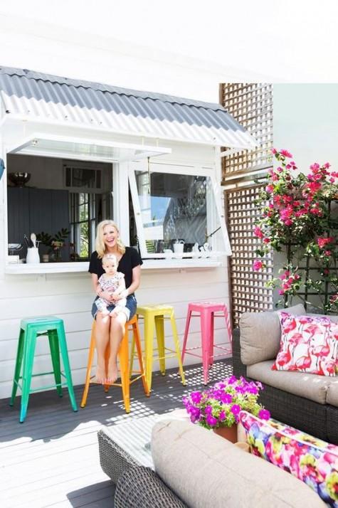 finestre in stile garage e un piccolo spazio per la colazione all'aperto, decorato con sedie in metallo colorato