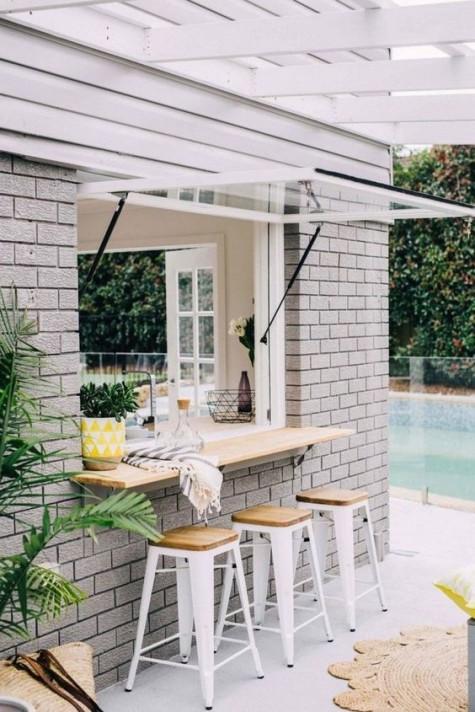 una finestra in stile porta del garage e uno spazio per la colazione all'aperto o un piano bar con sedie in metallo bianco e piani in legno