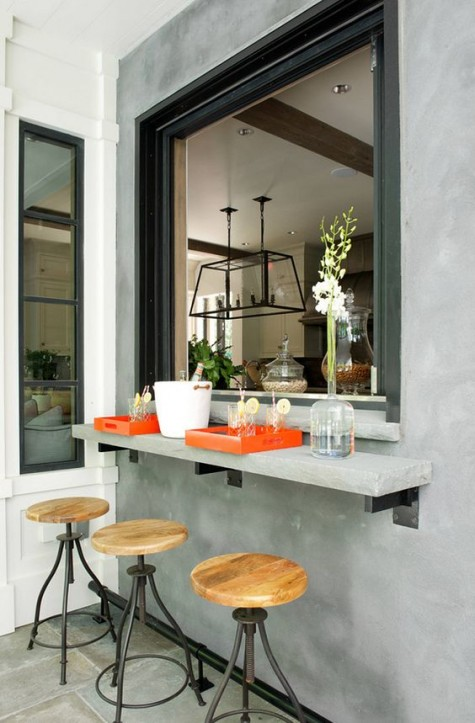 una finestra avvolgibile di grandi dimensioni e un piccolo ripiano in cemento e sgabelli in metallo e legno per un'atmosfera industriale