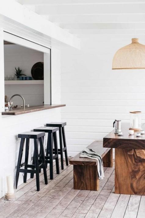 una piccola finestra avvolgibile, un piano del tavolo macchiato di scuro, sedie in legno nero per un bar all'aperto e una zona pranzo adiacente