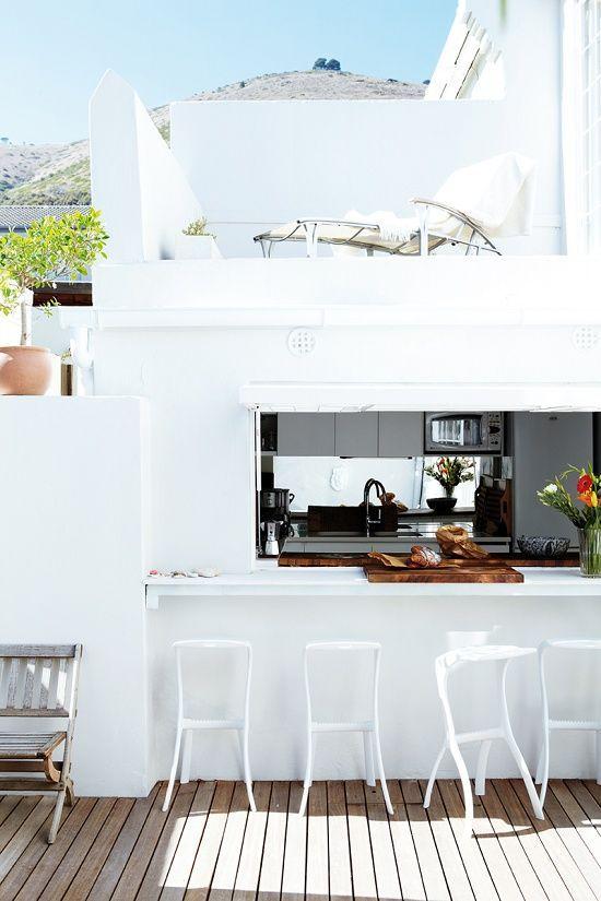 una finestra avvolgibile, un piano del tavolo bianco e sgabelli bianchi per uno spazio esterno luminoso e minimalista