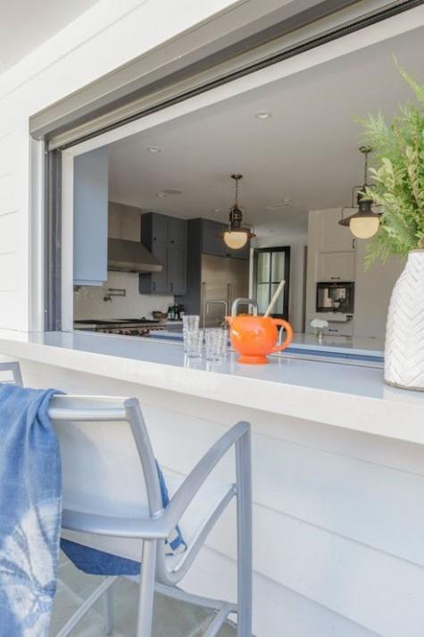 una finestra avvolgibile con un piano di lavoro bianco e comode sedie è l'ideale per consumare un pasto all'aperto