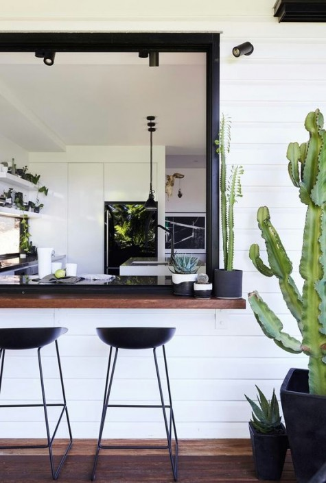 una finestra scorrevole con cornice nera e un ripiano del tavolo macchiato di scuro con cactus, sgabelli in metallo nero per un look chic