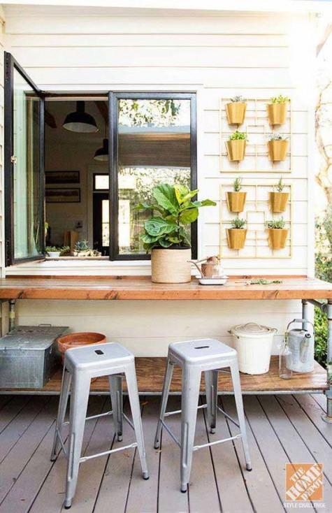 una normale finestra e un tavolo da giardino usato come piano per una finestra passante, un orto di erbe aromatiche proprio sul muro