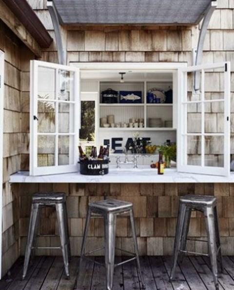 una normale finestra, un tavolo bianco e sedie in metallo compongono uno spazio industriale fresco e audace