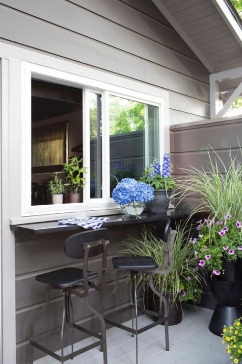 finestre scorrevoli e un davanzale stretto e lucido come sgabelli industriali da bar plsu in metallo scuro e fiori in vaso