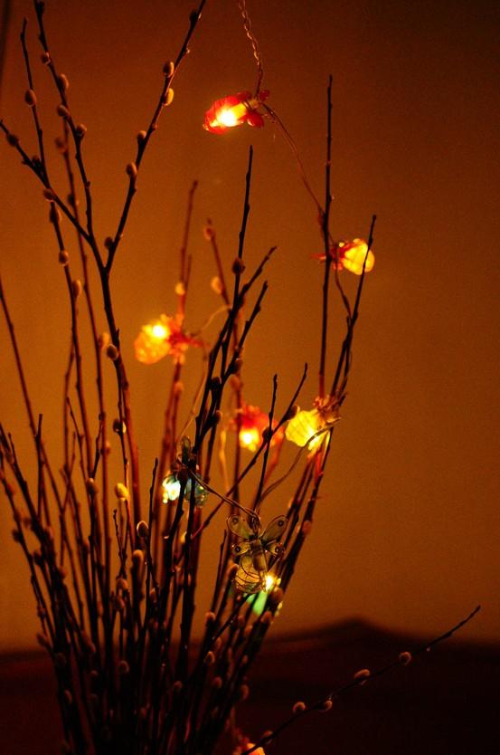 una disposizione dei rami con varie luci accattivanti è un'idea divertente per una camera da letto o un altro spazio