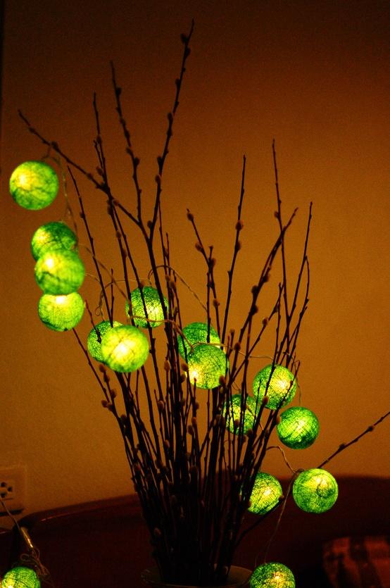 una disposizione dei rami con luci avvolte verdi è un'idea creativa e unica