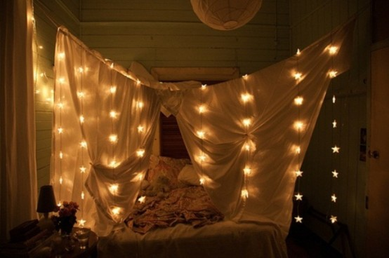 tende intorno al letto con luci a forma di stella per un'atmosfera romantica